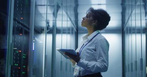 Formal African American woman using tablet while working with server rack in contemporary data center hallway