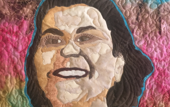 Quilt featuring the face of Claudine Michel with a rainbow background